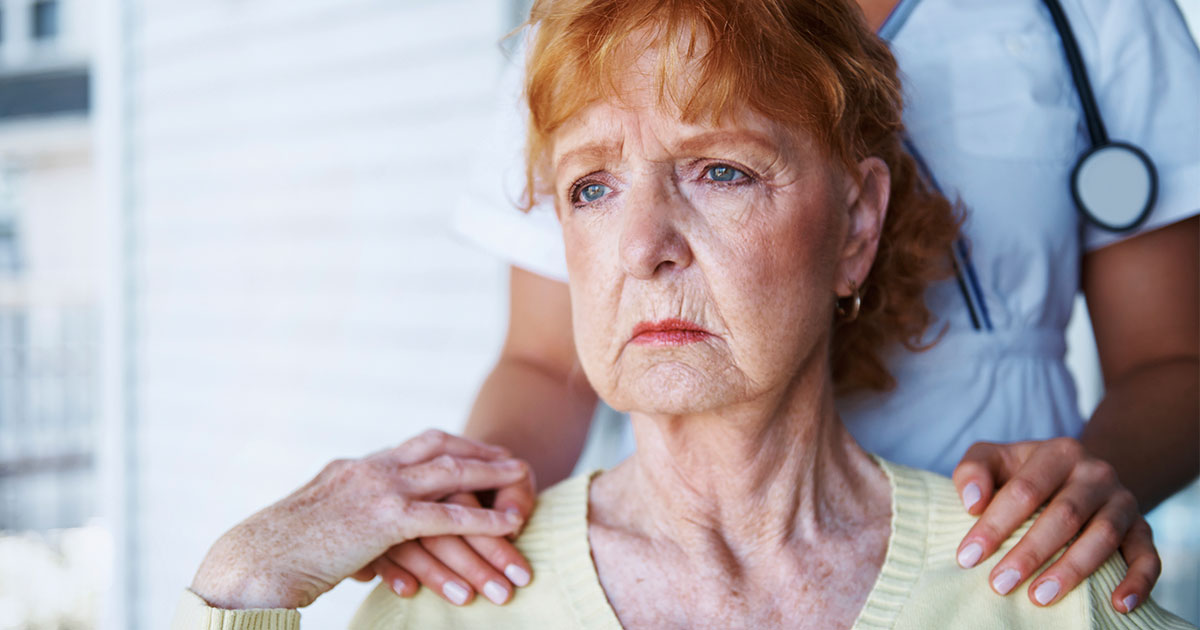 Anxious senior woman being comforted by doctor