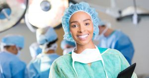 Smiling surgeon with a team of surgeons in the background