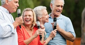 Group of senior friends having a party in the backyard, doing karaoke