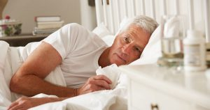 Sick mature man lying in bed