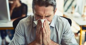 Man blowing his nose with a kleenex