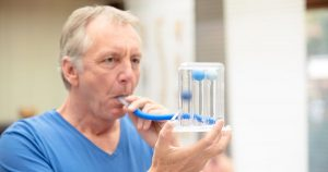 Man blowing into a spirometer