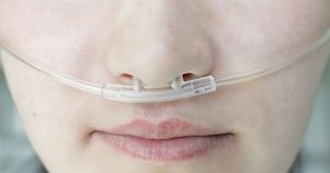 Person wearing oxygen nose tube