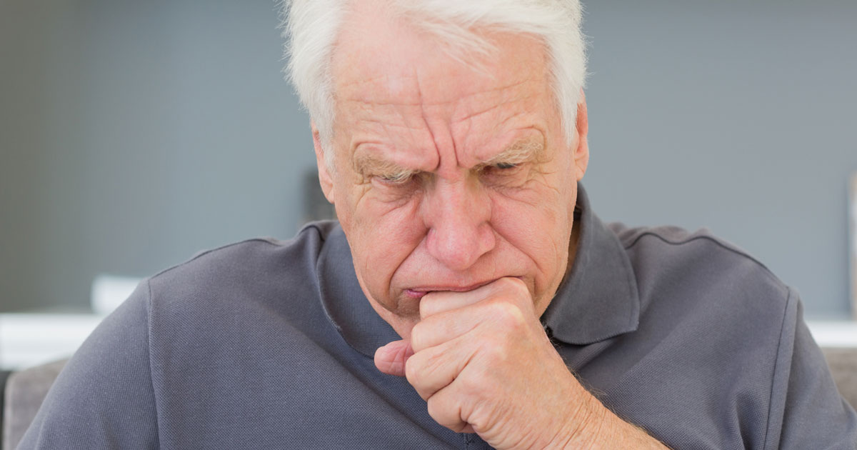 A senior man is coughing