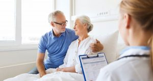 Husband is hugging wife, who is sitting up in a hospital bed, while doctor fills out charts