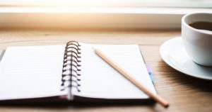 Open notebook with pencil on top