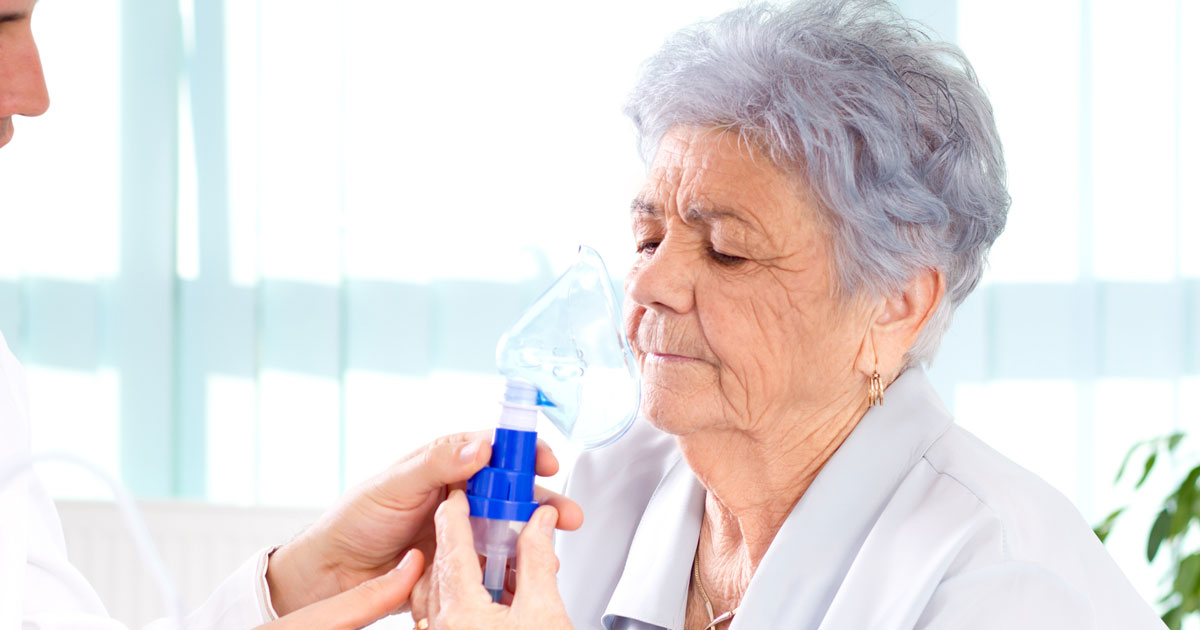 Doctor showing patient how to use an oxygen mask