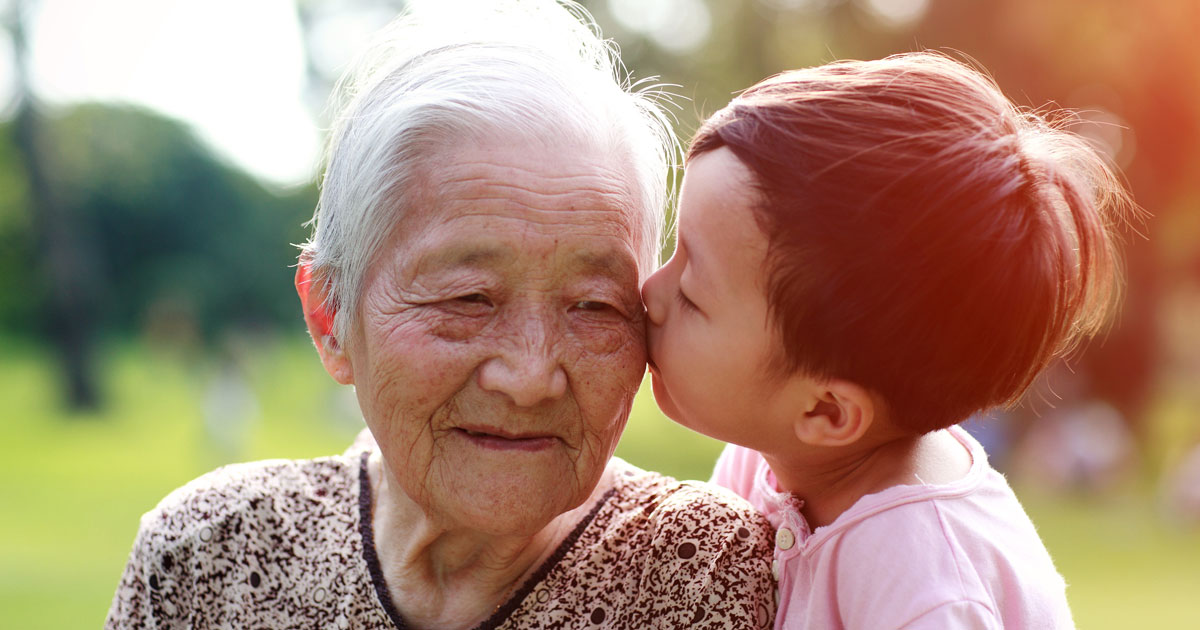 Grandchild gives his grandmother a kiss