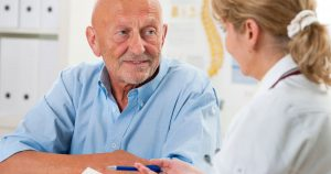 Older male patient talking to doctor
