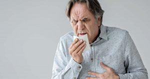 Senior man coughing into a kleenex