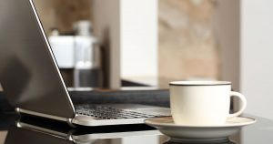 An open laptop with a coffee cup beside it