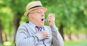 An older man is using his emergency inhaler