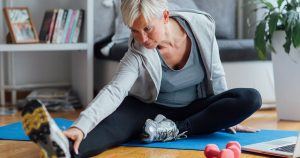 A woman is doing stretches at home