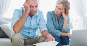 Stressed couple looking at financial bills