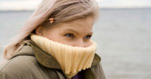 Mature woman covering her face from the cold wind