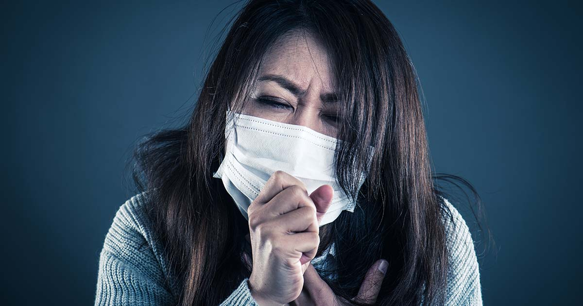 Woman wearing a surgical mask is coughing