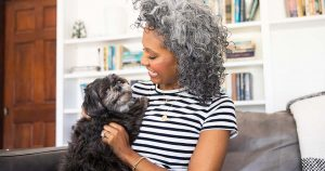 Woman with white curly hair cuddles on the couch with her dog