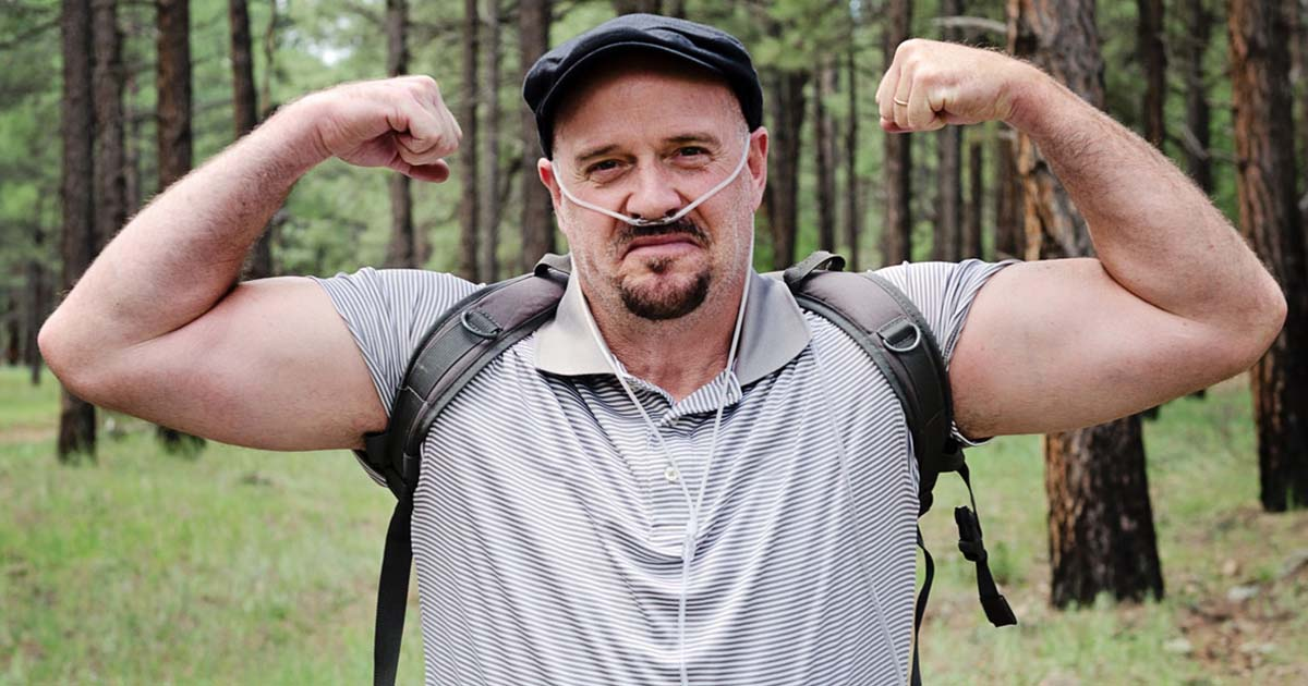 Man wearing oxygen nose tubes is outside flexing his muscles