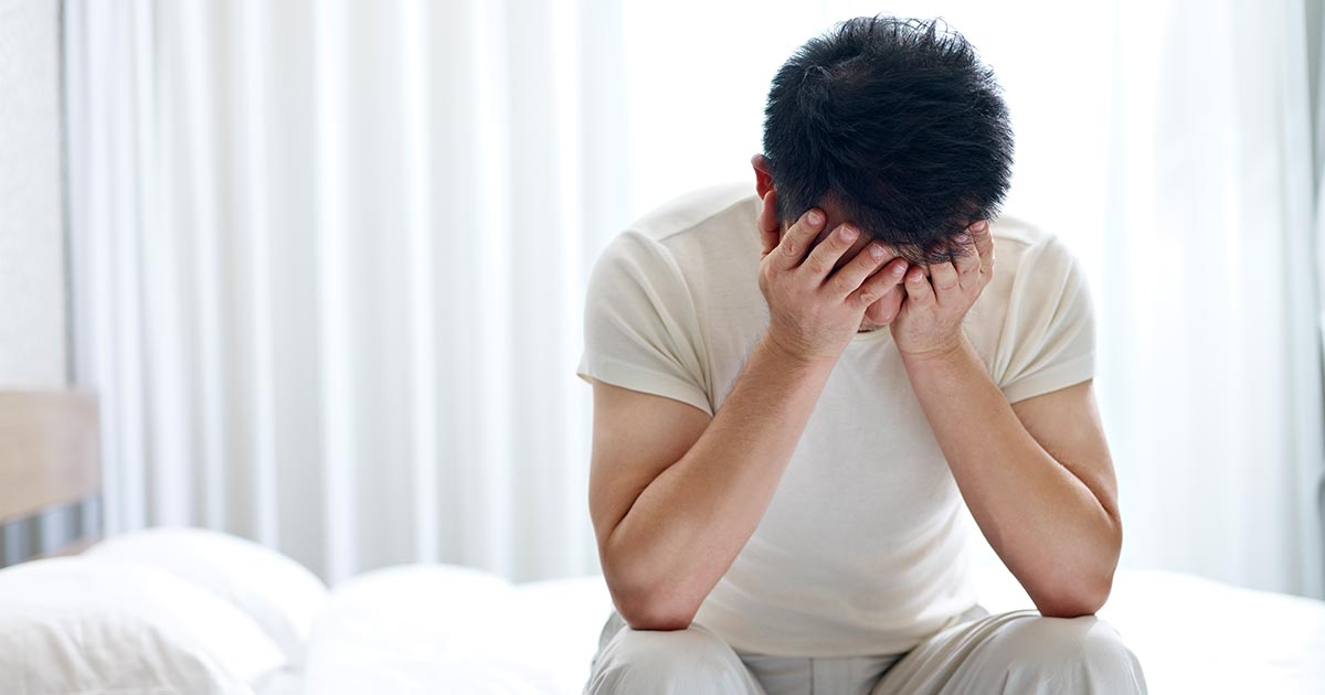 Man suffering from insomnia sitting on bed head down covering face with hands