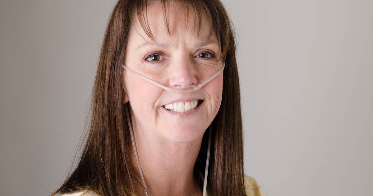 Smiling woman wearing an oxygen nose tube
