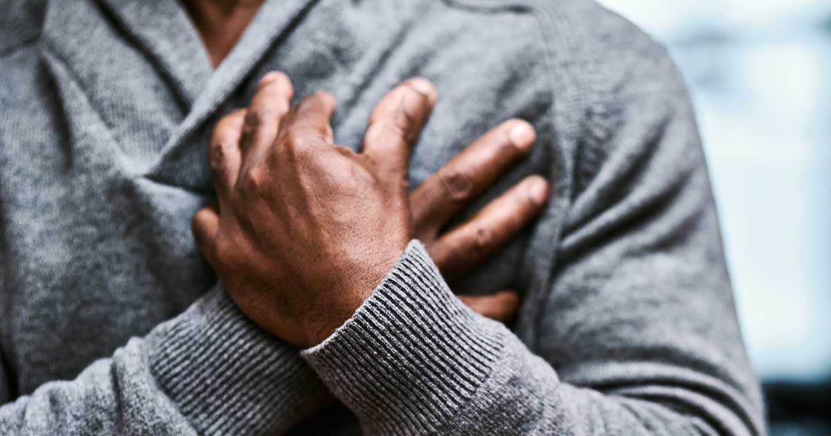 Man clutching his chest while experiencing chest discomfort or pain