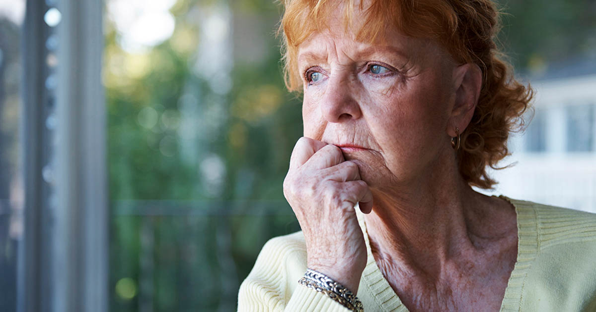 Anxious mature woman looking out window