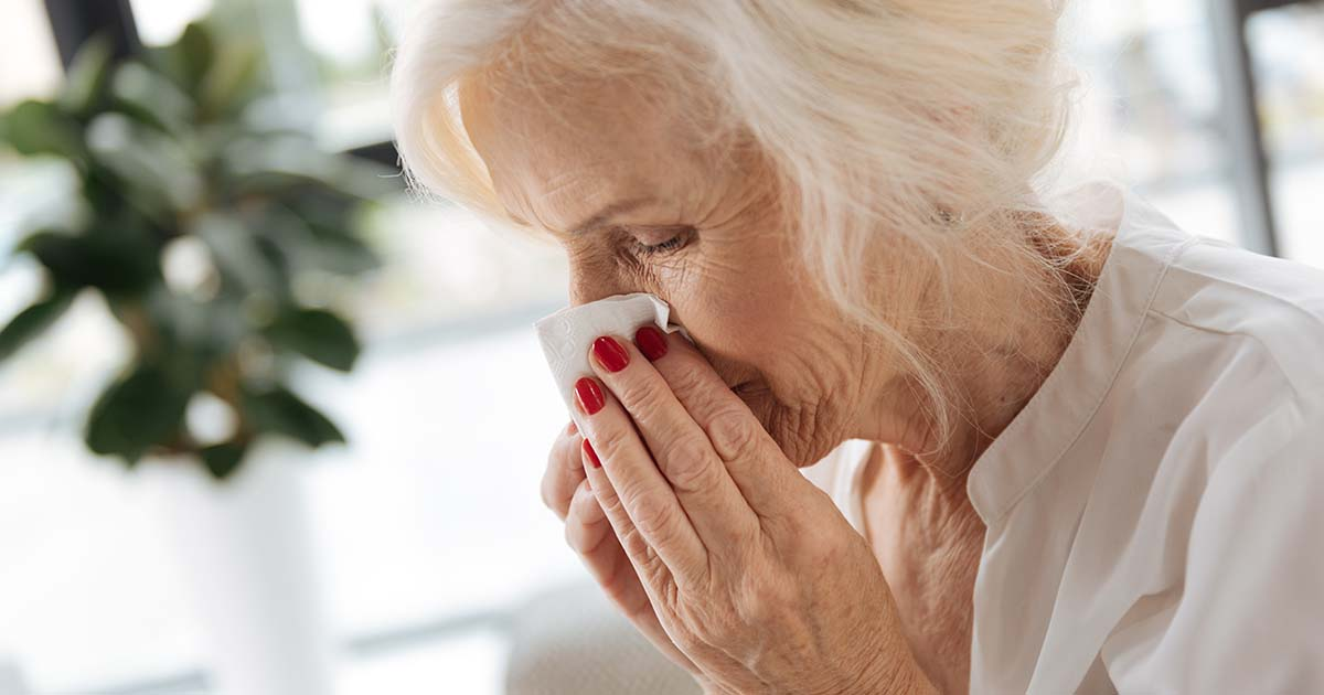 Senior woman blowing her nose into a kleenex
