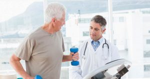 Doctor watches over senior man undergoing rehabilitation