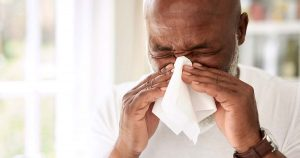 Mature man blowing his nose at home