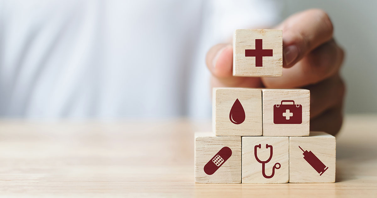 Hand arranging wood block stacking with healthcare icons