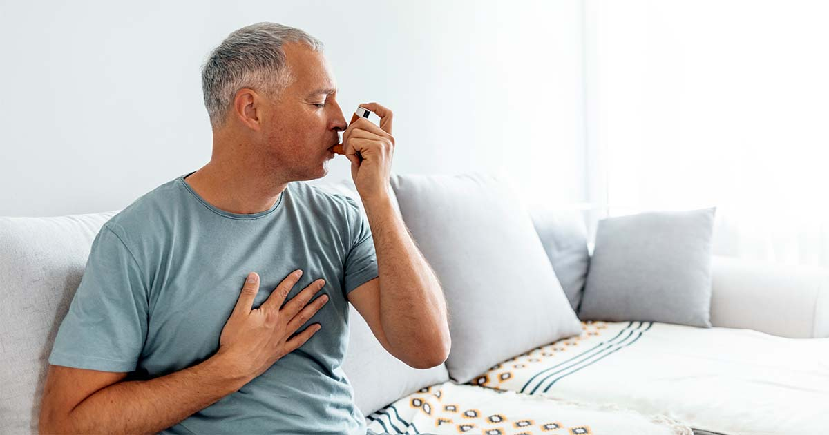 A man sitting on a couch while breathing into an inhaler.
