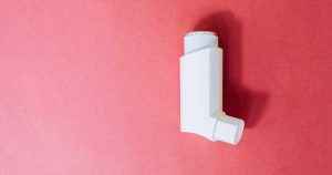 A white inhaler against a red background.